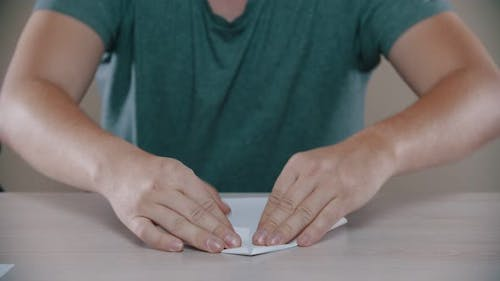 Man Is Folding a Paper Airplane on the Table