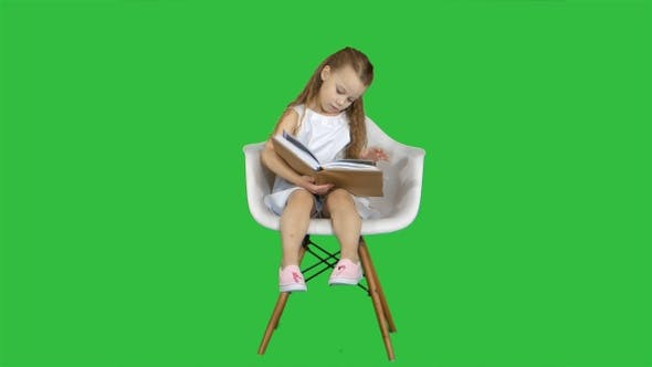 Thumbnail for Little Student Girl Sitting and Reading Book on A Green