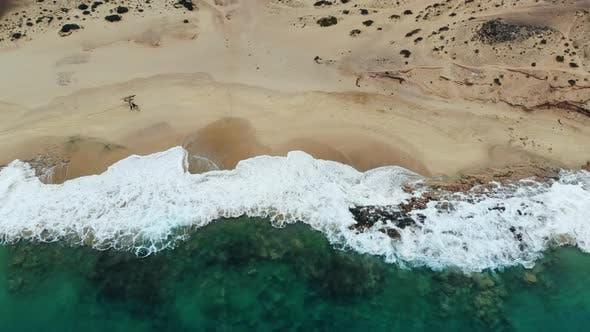 Aerial View Waves Break on White Sand Beach