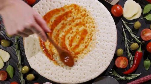 Chef Spreading Tomato Sauce on Pizza Dough in Pizza Restaurant