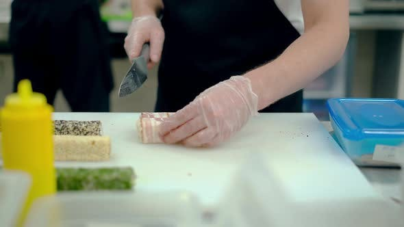 Cook Cuts a Japanese Roll with Bacon.