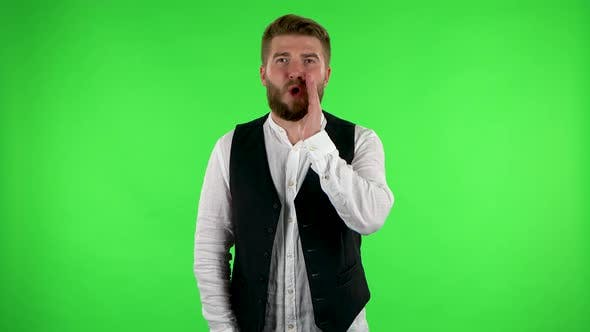 Thumbnail for Man Screams Calling Someone on a Green Screen at Studio.
