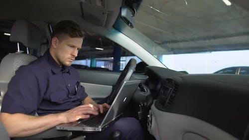 Männlicher Polizeibeamter arbeitet am Laptop im Auto und füllt Daten im Kriminalbericht