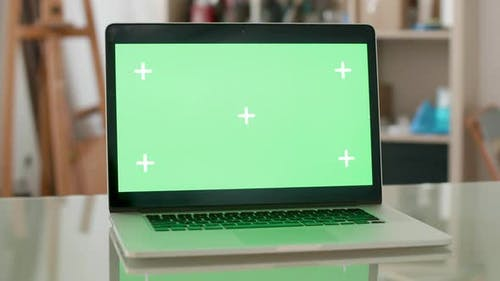 Parallax Shot of a Laptop with Green Screen on and People on the Background
