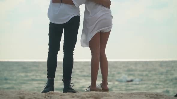Thumbnail for Pairs of Slender Legs of a Young Hugging Guy and Girl on the Beach of Ocean in Windy but Warm