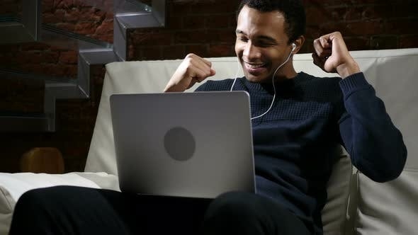 Cover Image for African Man Listening Music on Laptop and Dancing at Night