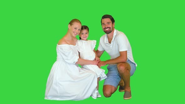 Adorable Caucasian Family Woman and Man with Little Girl Smiling and Posing Together on Camera on a