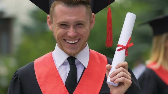 Thumbnail for Happy and Proud Graduating Student Holding Higher Education Certificate in Hand