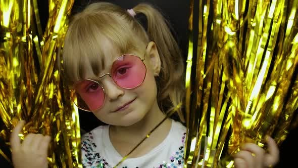 Portrait of Happy Child Playing, Fooling Around in Foil Fringe Golden Curtain. Little Blonde Kid