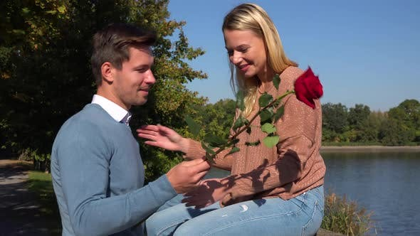 Thumbnail for A Man Gives a Red Rose To His Girlfriend in a Park on a Sunny Day