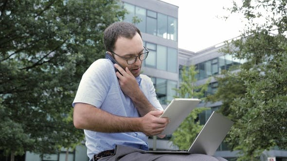 Cover Image for Business man using tablet and laptop while talking on smartphone