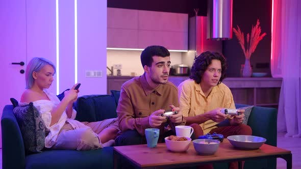 Thumbnail for Guys Playing Video Game While Girl Using Smartphone for Social Media. Friends Spending Time Together