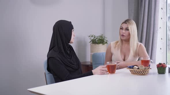 Thumbnail for Serious Caucasian Blond Woman Listening To Muslim Friend and Giving Advice. Friendship and Support
