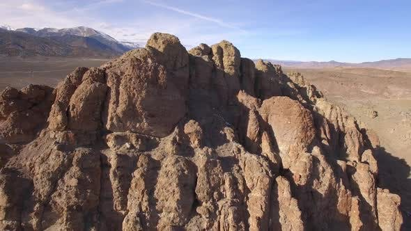 Aerial panning view of rocky desert mountain in vast landscape