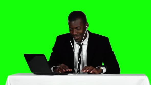 Cover Image for Businessman Sitting at a Desk and Listening To Music on Headphones. Green Screen