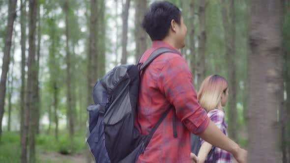 Hiker Asia backpacker couple adventure feeling freedom walking in forest, enjoy their holidays.