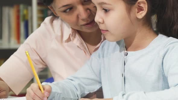 Cover Image for Close Up of a Cute Little Girl Studying with Her Mother