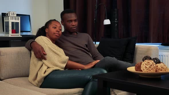 Thumbnail for Young Black Happy Couple in Love Watch Television in Living Room - Man Switches