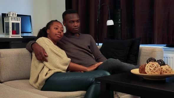 Thumbnail for Young Black Happy Pärchen in Love Fernsehen im Wohnzimmer - Mann Schalter