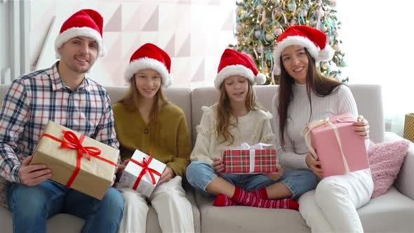 Glückliche junge Familie mit Kindern, die Weihnachtsgeschenke halten