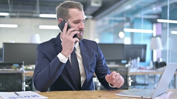 Thumbnail for Young Businessman Talking on Smartphone in Office