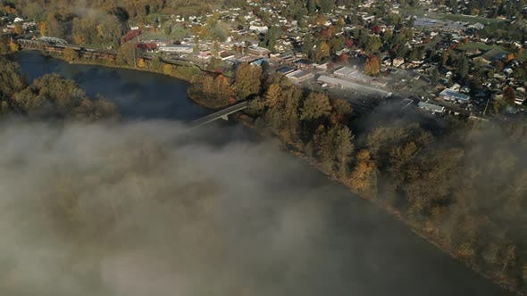 Cover Image for Small Town By River Aerial With Train Traveling In Lowland Fog