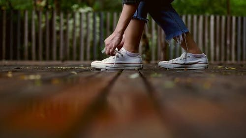 Young Asian woman trying on white sneakers at a public park on a rainy day.
