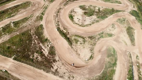 Professional racer is riding motorbike through the hilly track