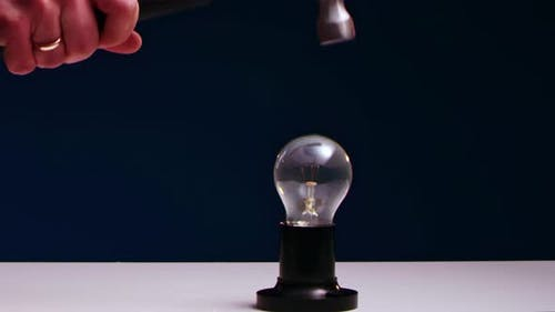 AMan's Hand Smashes Incandescent Light Bulb Lying on Table with Iron Hammer