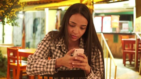 Latina woman texting on smartphone at restaurant - product preview 0