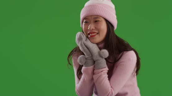 Thumbnail for Close up of joyful asian woman dressed for winter season on green screen