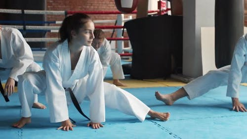 Four Kickboxers Stretching Legs in Sport Center