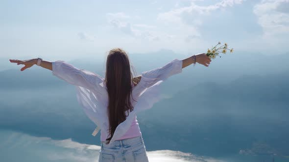 Mountains and a Lake with a Girl Dressed in White Blowing in the Wind