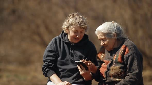 Thumbnail for A Woman Teaches Her Old Mother To Use a Smartphone. Portrait of Two Women Looking at Smartphone