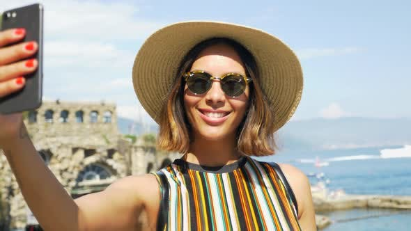 Thumbnail for A woman takes selfies and uses facetime video calling in a luxury resort town in Italy, Europe.