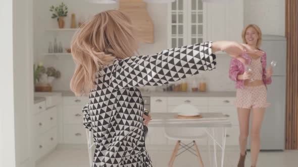 Thumbnail for Two Beautiful Blonde Caucasian Women Dancing with a Bottle of Wine and Two Glasses at the Kitchen