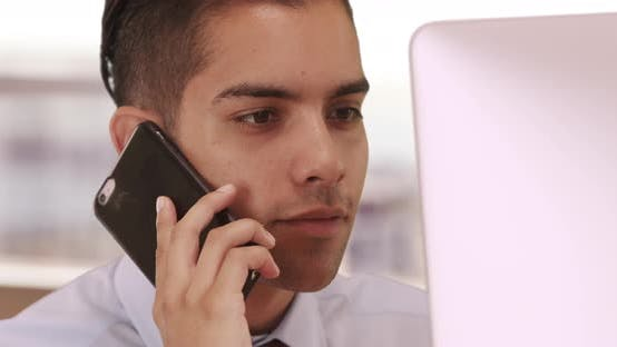 Thumbnail for Hispanic Business man on cell phone and computer with