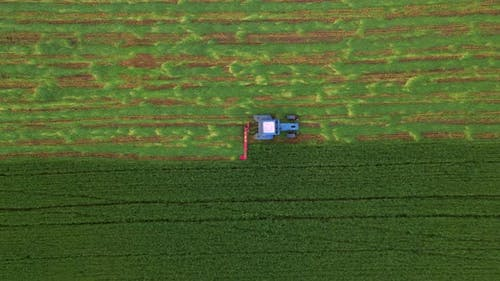 Top Down Aerial View of Mowing with a Agriculture Machine Tractor with Mowers on the Big Farm Field