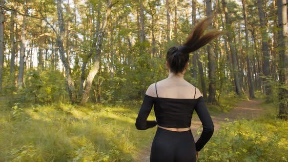 Young Woman Makes a Morning Jog in the Forest City Park