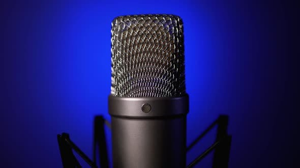 Thumbnail for Studio Condenser Microphone Rotates on Blue Background.