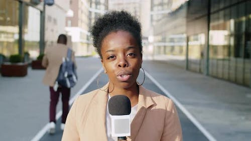 Afro-American Female Journalist Presenting News at Camera
