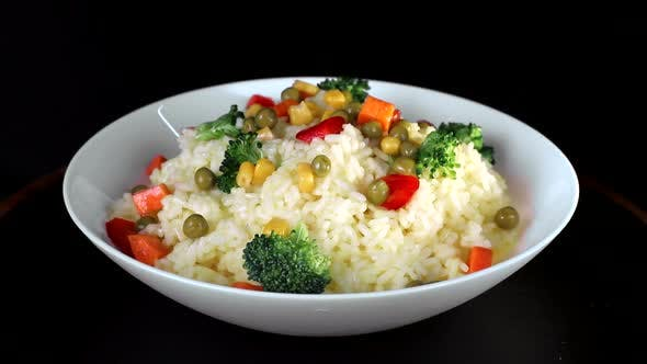 Thumbnail for Rice with Pieces of Vegetables, Greens and Red Pepper on a White Plate Rotates on a Black Background