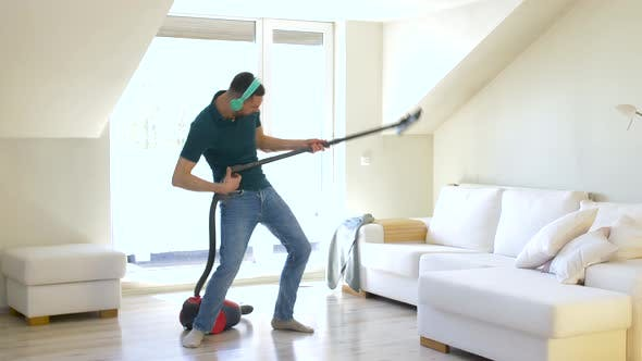 Cover Image for Man with Vacuum Cleaner and Headphones at Home
