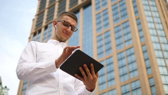 Thumbnail for Businessman In Wireless Earphones Using A Tablet Computer In City