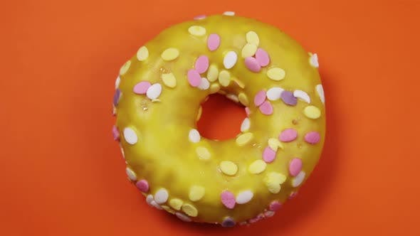 Donut with Icing on an Orange Background