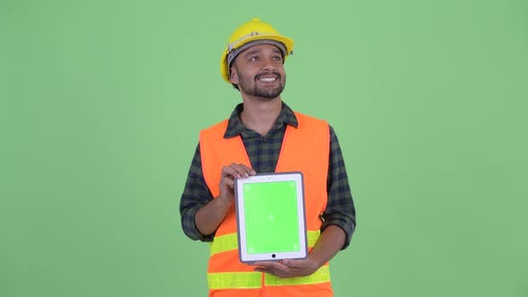 Thumbnail for Happy Young Bearded Persian Man Construction Worker Thinking While Showing Digital Tablet