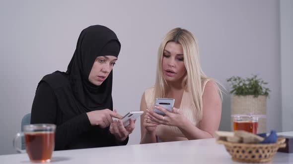 Thumbnail for Two Young Women From Different Cultures Using Social Media on Smartphones. Muslim and Caucasian Lady