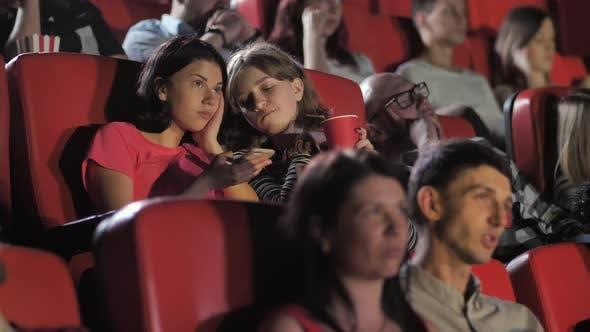 Teen Girls Using Smartphone During Movie in Cinema