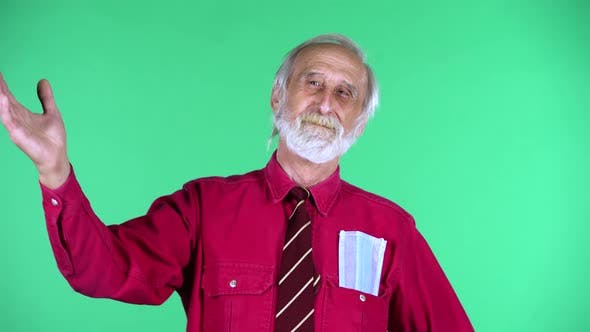 Thumbnail for Porträt des glücklichen alten Mannes 70er Jahre winkende Hand und zeigt Geste hierher kommen, isoliert über Grün