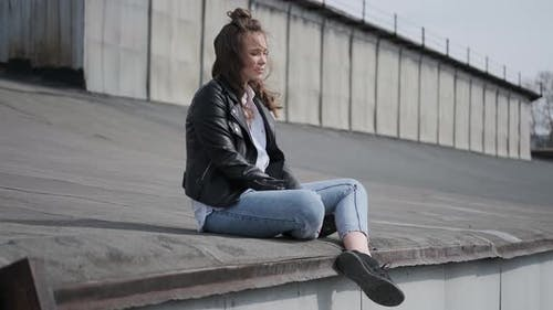 Hipster Girl Sits on the Roof and Enjoys a Warm Spring Day.